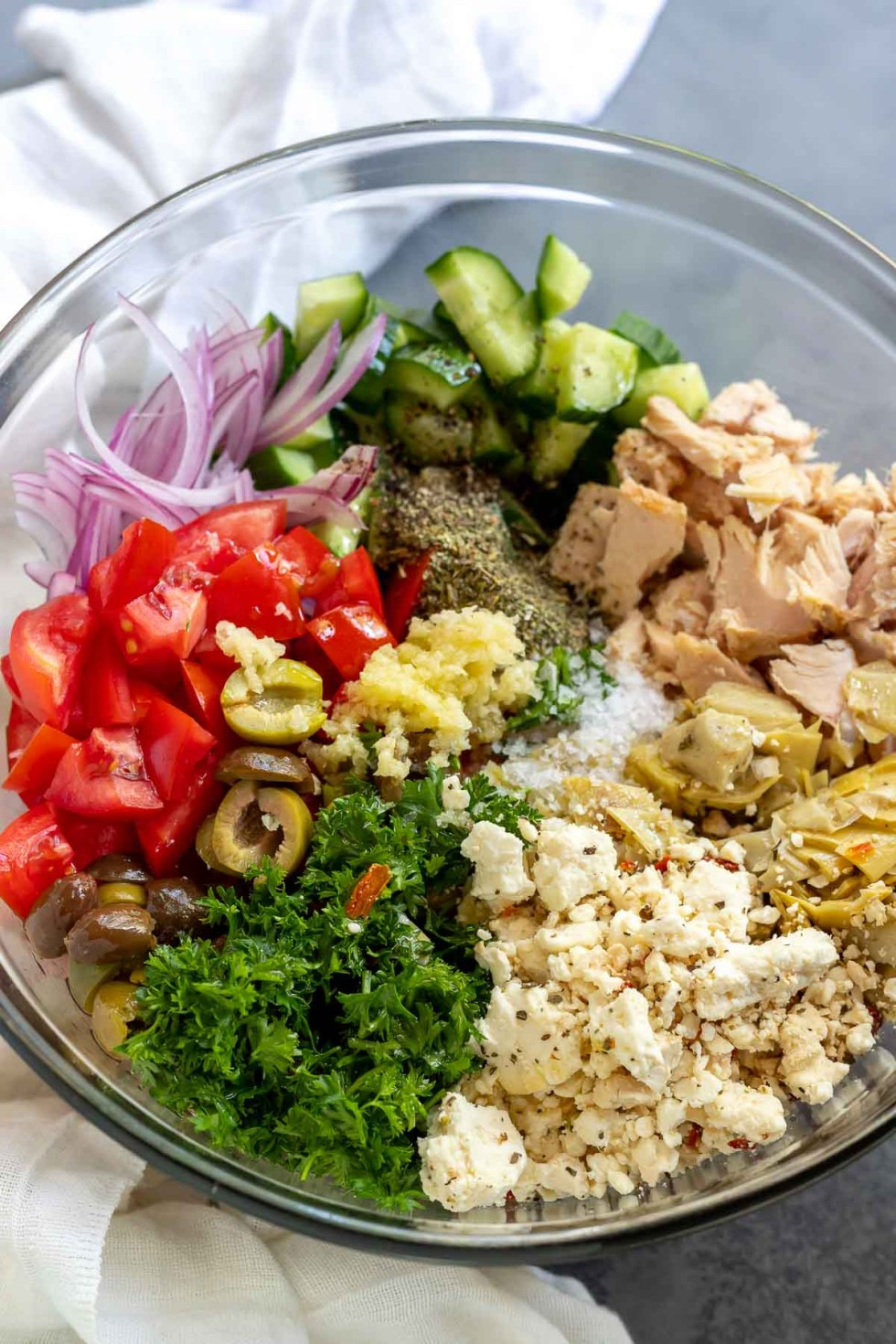tuna salad ingredients in clear glass bowl