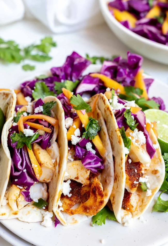 three fish tacos on white plate