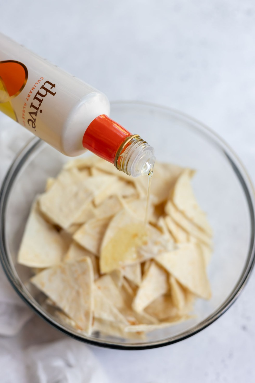 tortilla triangles being drizzled with oil