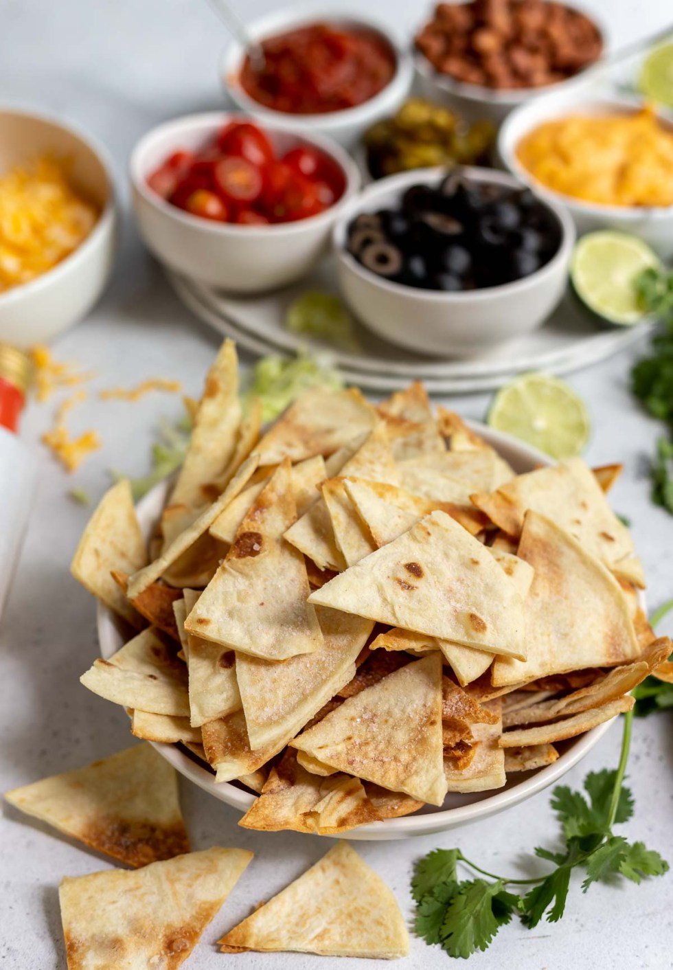 homemade tortilla chips in white bowl with nacho fixins in the background