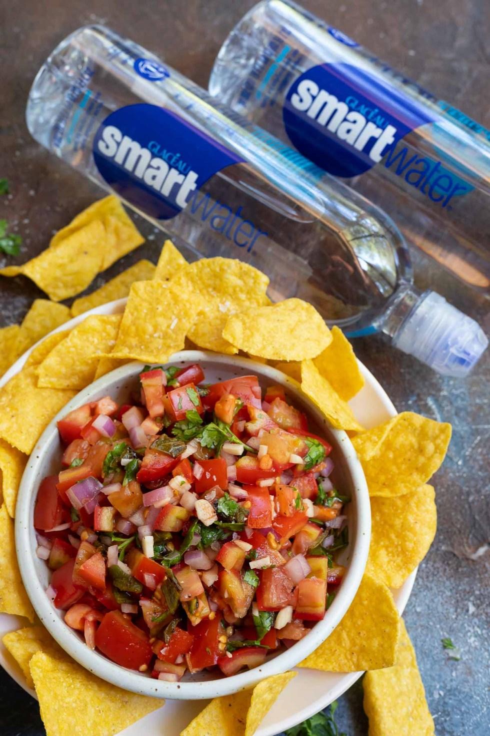 bowl of fresh salsa next to water bottles