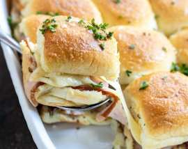 ham cheese slider being lifted out of casserole dish