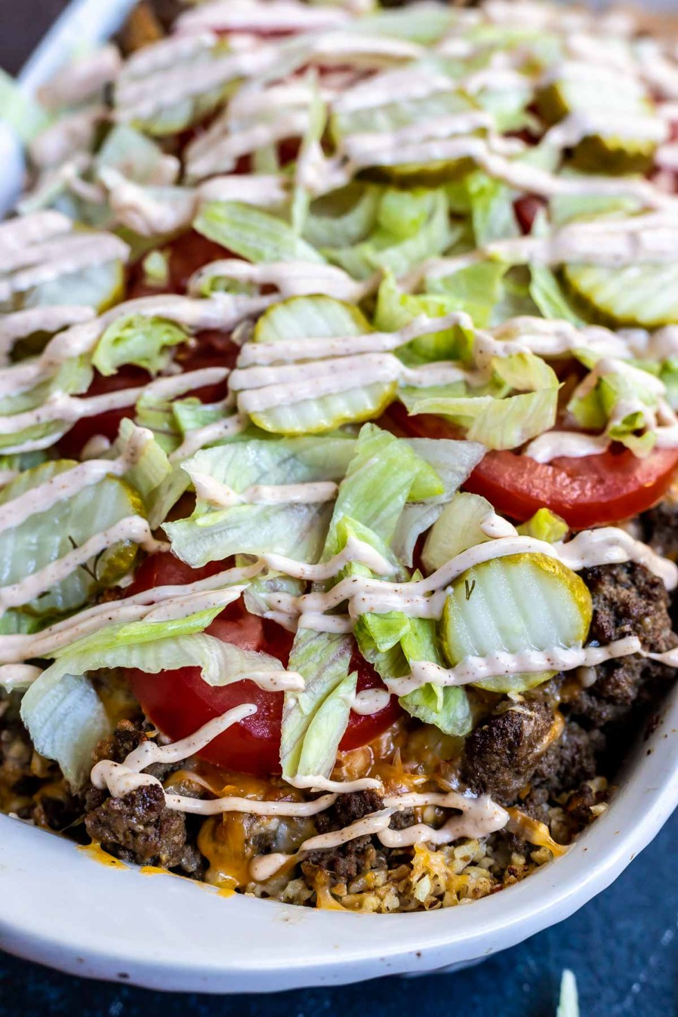 cheeseburger casserole topped with lettuce and pickles