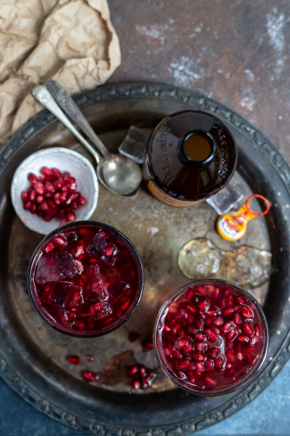 mule cocktails on tarnished silver tray along with pomegranate seeds and ginger beer