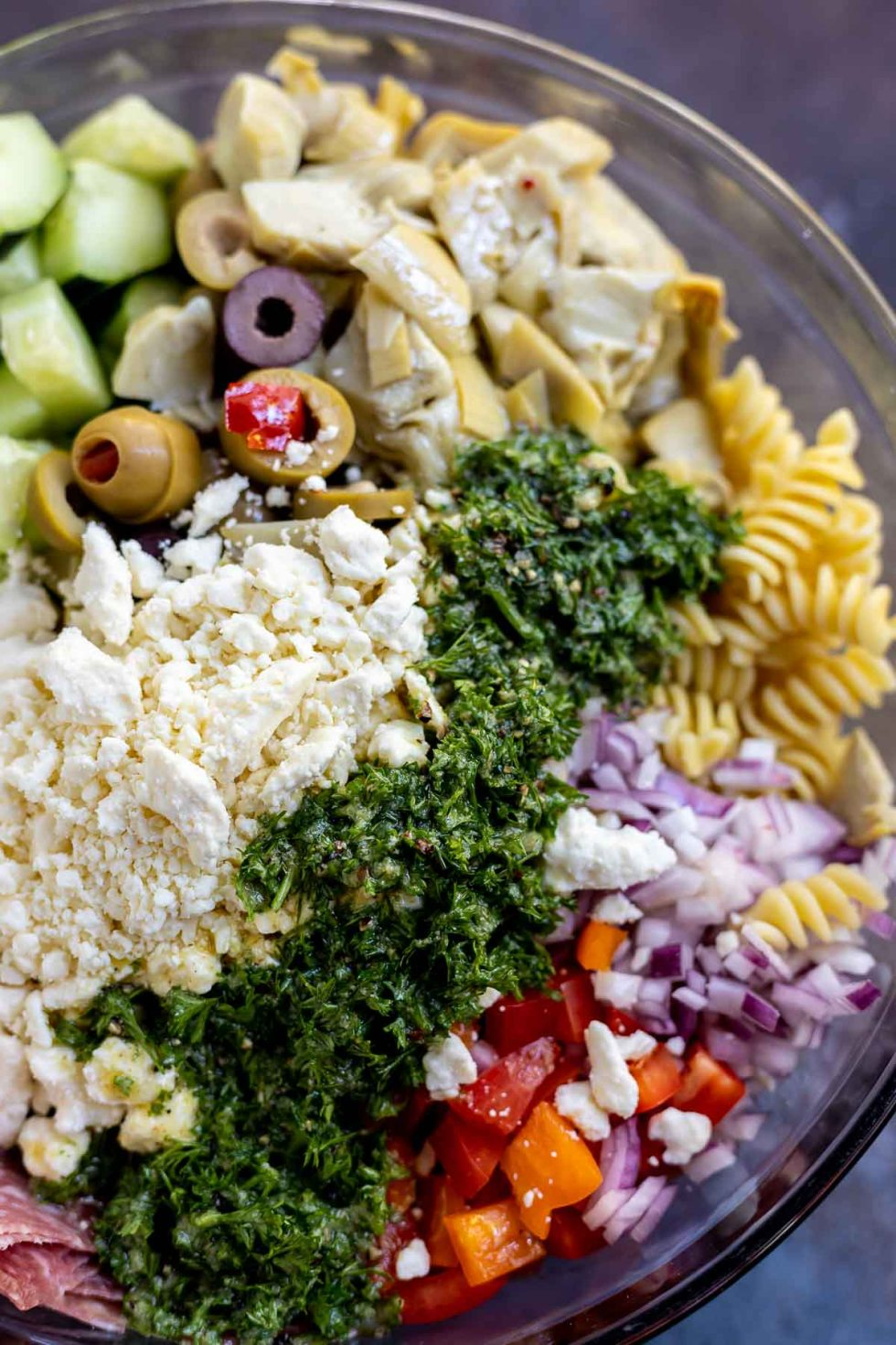 greek pasta salad ingredients topped with dressing