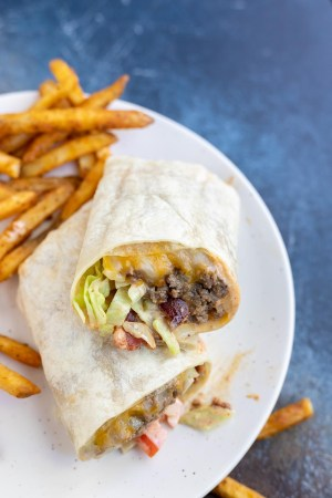burger wrap with fries served on white plate