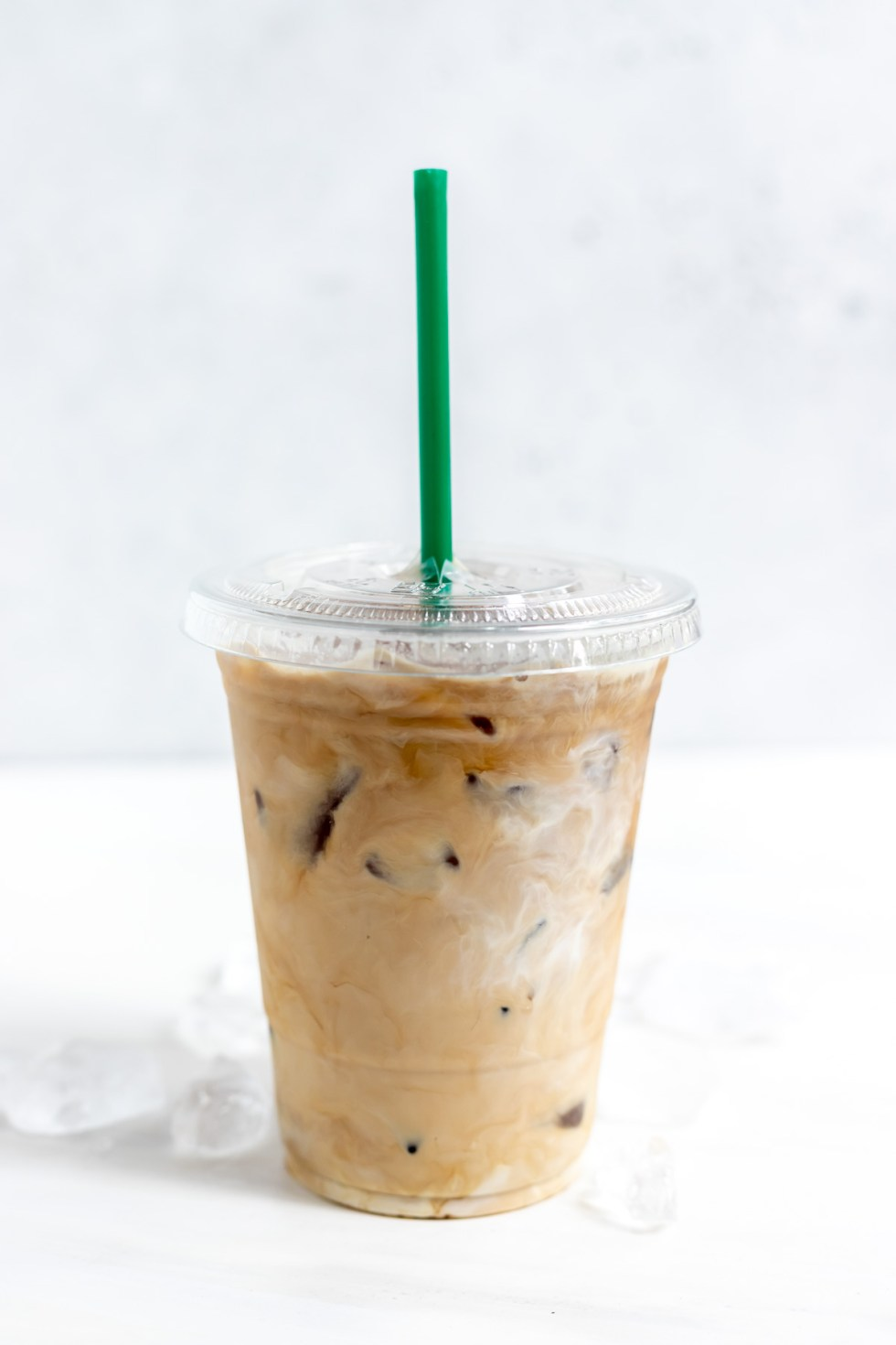 clear plastic cup filled with creamy coffee