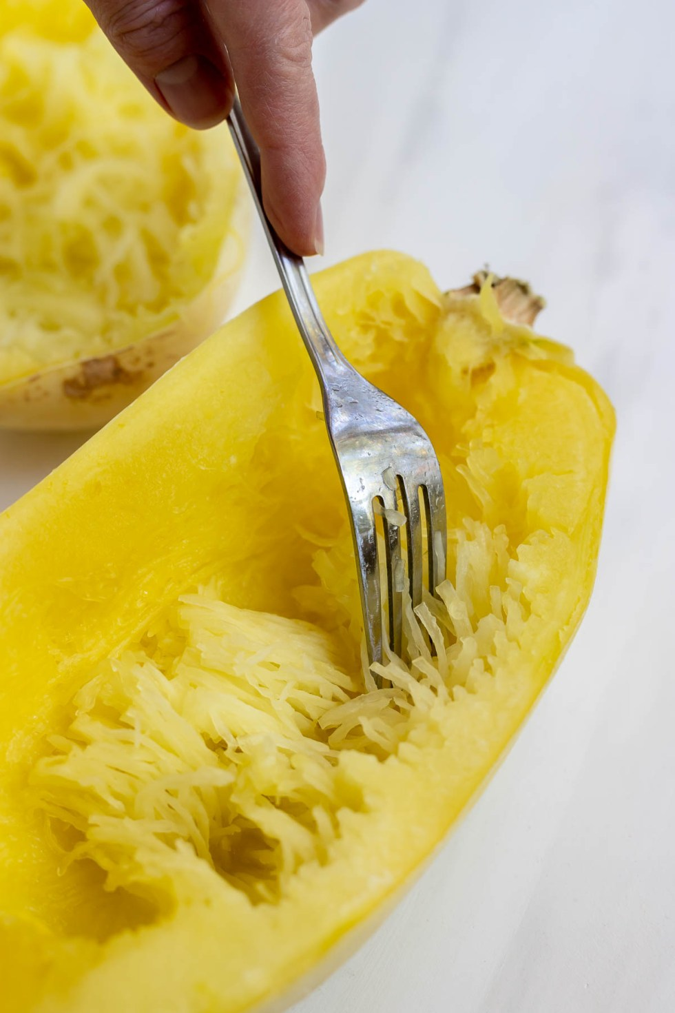 hand scraping cooked spaghetti squash with fork