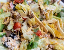 taco salad mixed together in white bowl