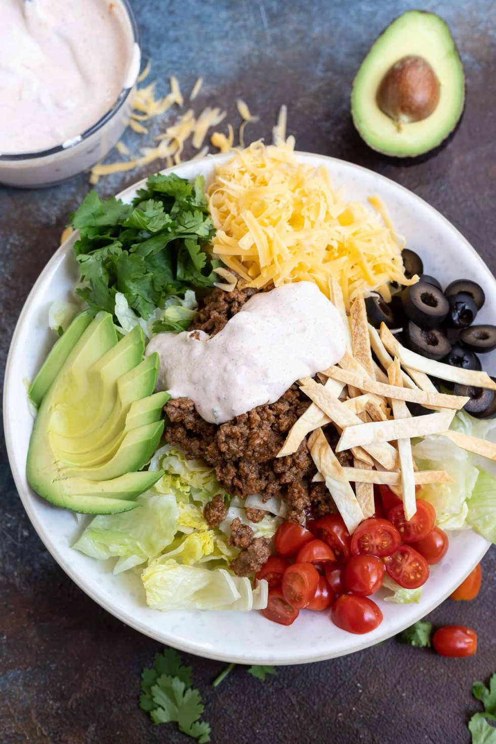 taco salad ingredients topped with dressing in white bowl