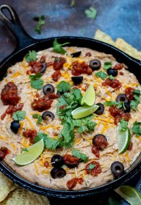 hot bean dip topped with black olives, cilantro, salsa, limes and shredded cheese in cast iron pan