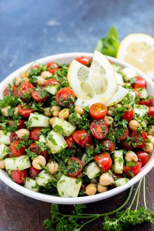 chickpea tabouli salad topped with lemon slices served in white bowl