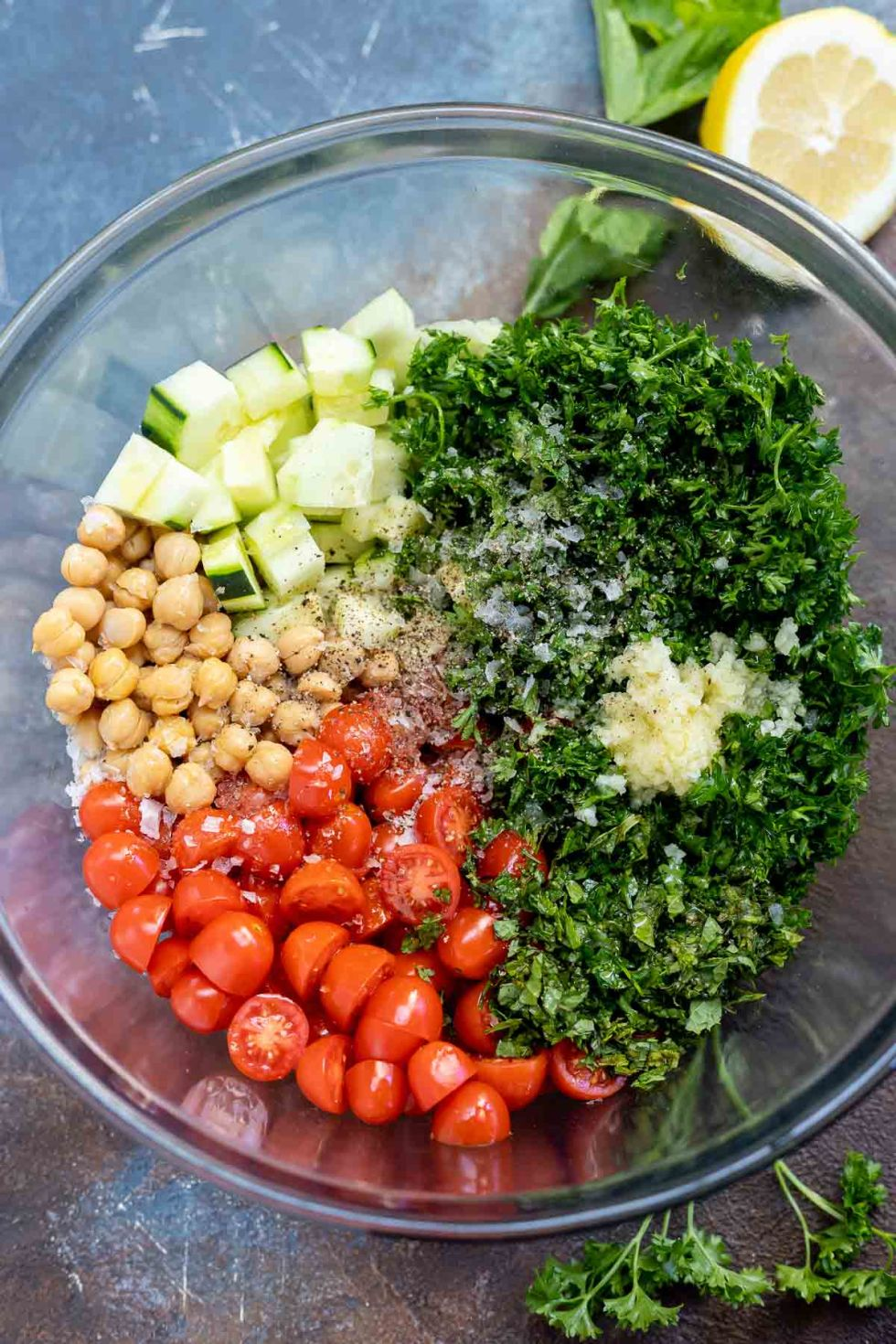 ingredients for garbanzo bean salad in clear glass bowl