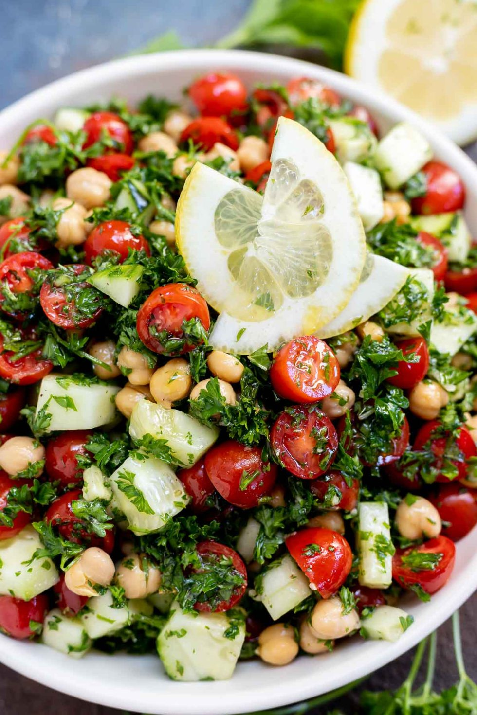 white serving bowl filled with chickpeas, tomatoes, cucumbers and herbs topped with lemon slices