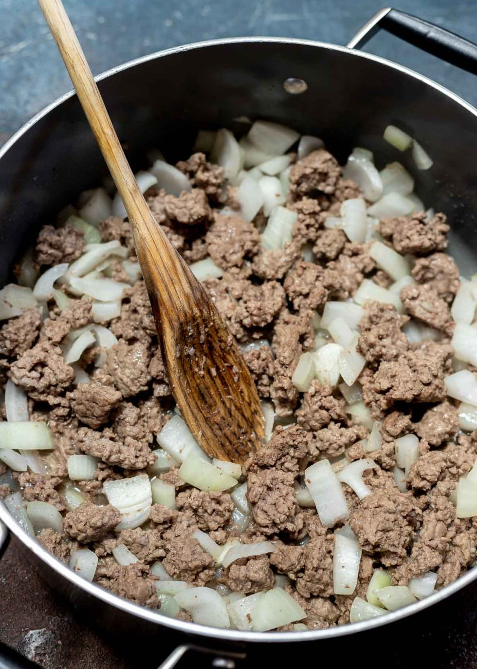 browned ground beef with chopped onions in pot with wooden spoon