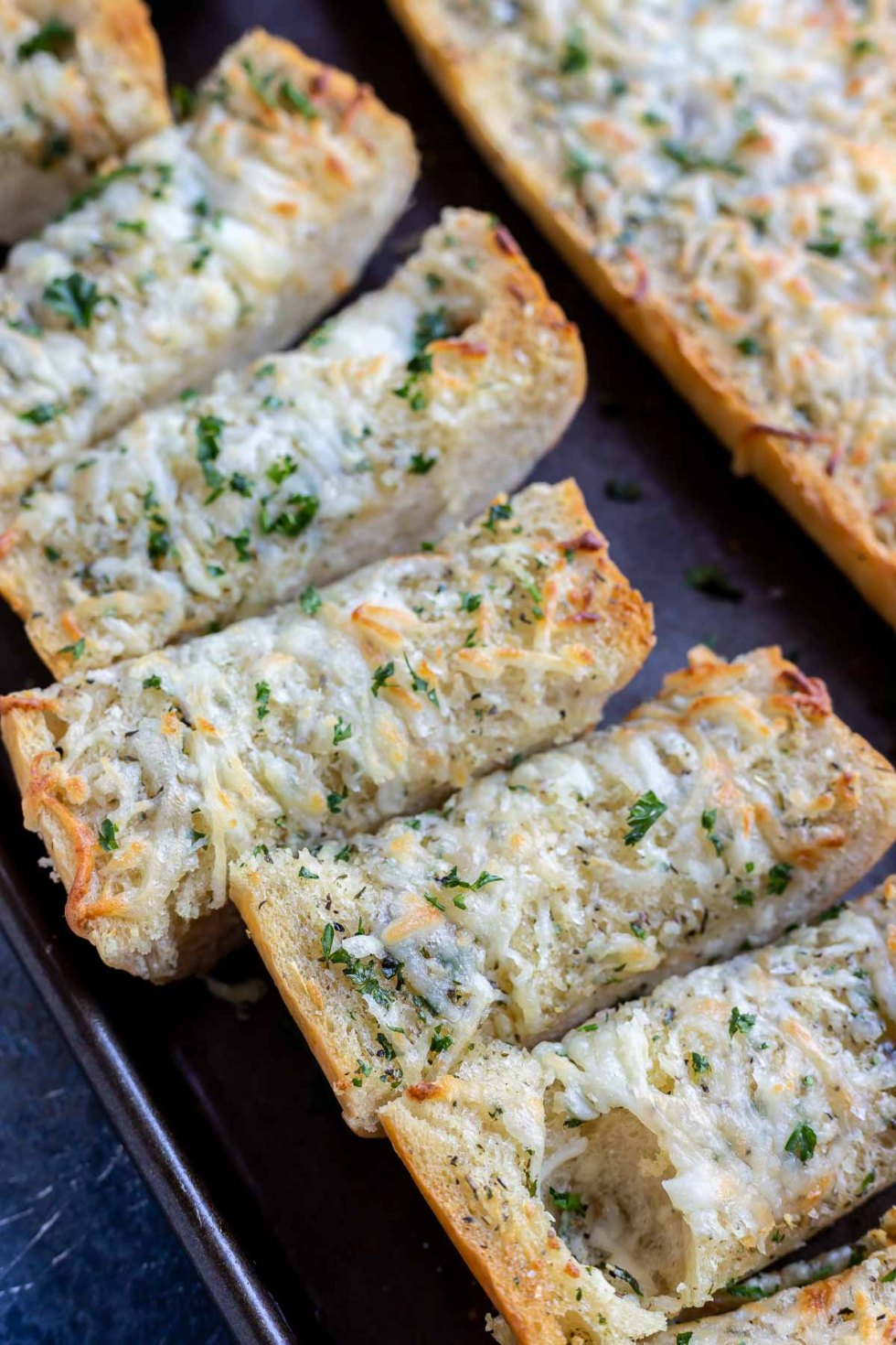 sliced French bread topped with melted cheese and parsley