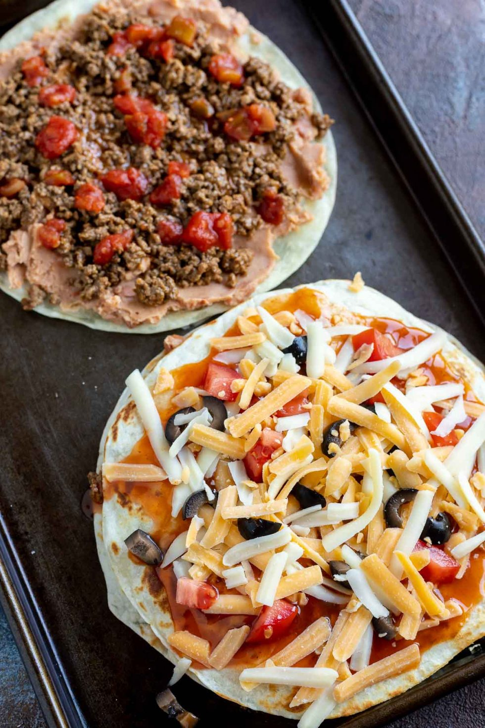 Mexican pizzas partially assembled on baking sheet
