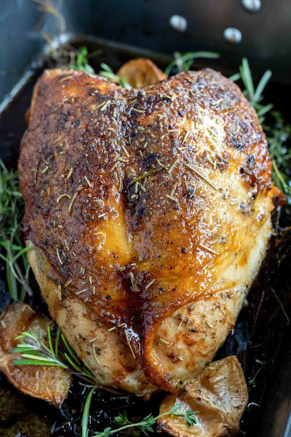 deep brown cooked turkey breast with herbs in roasting pan