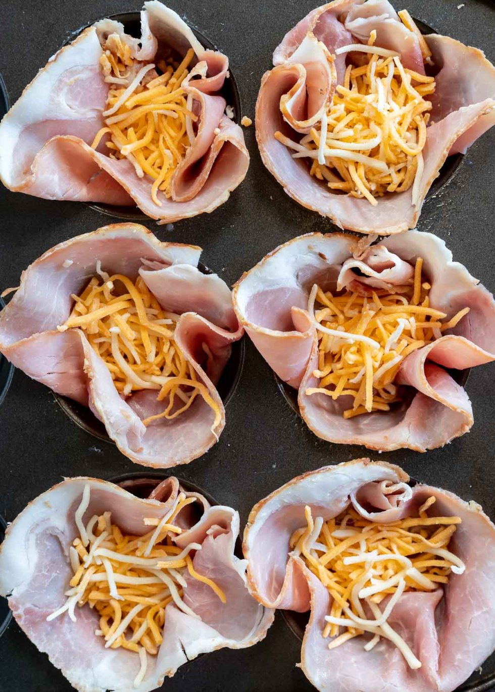 ham and shredded cheese in muffin tin