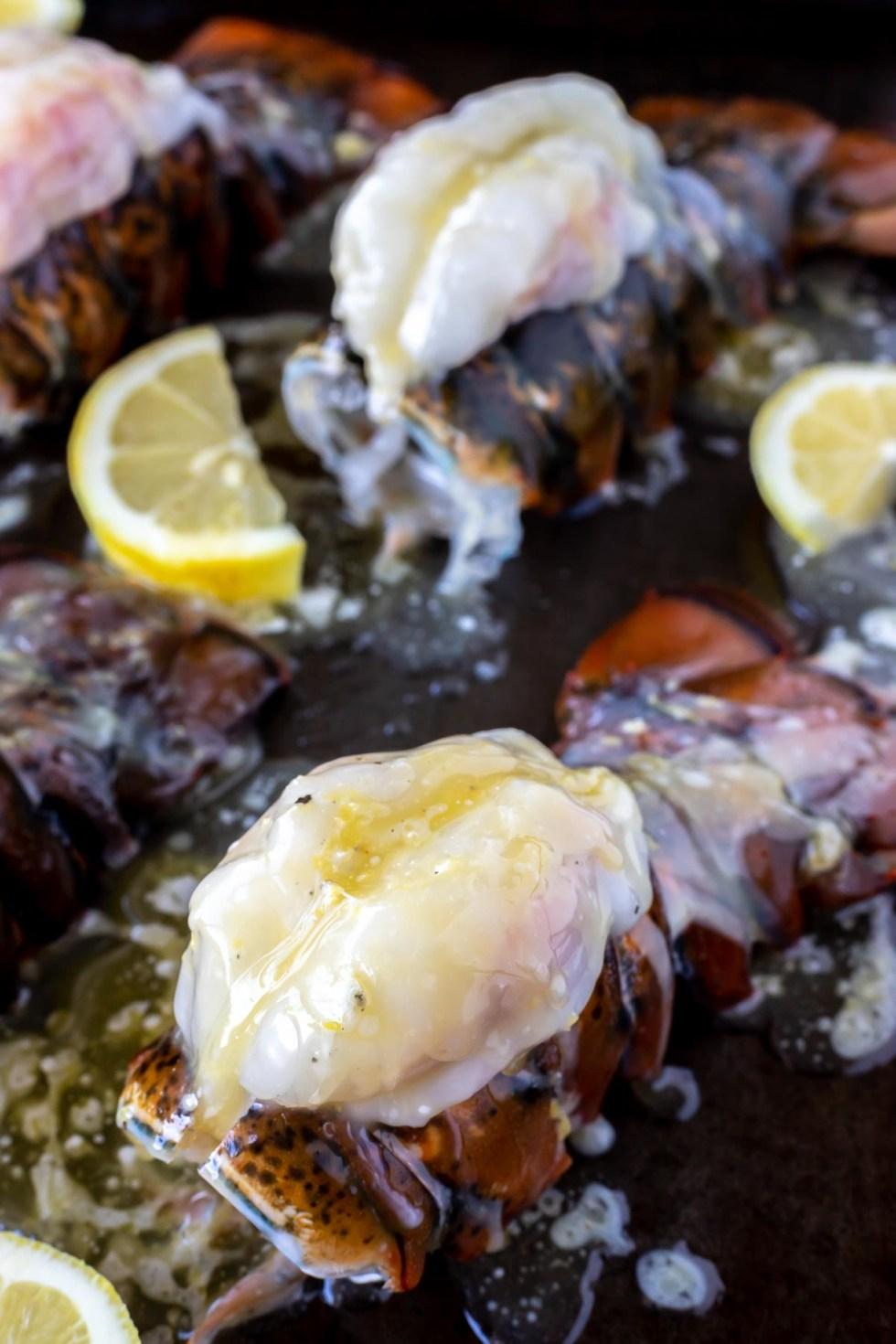 prepped buttery lobster and lemons on rimmed baking sheet