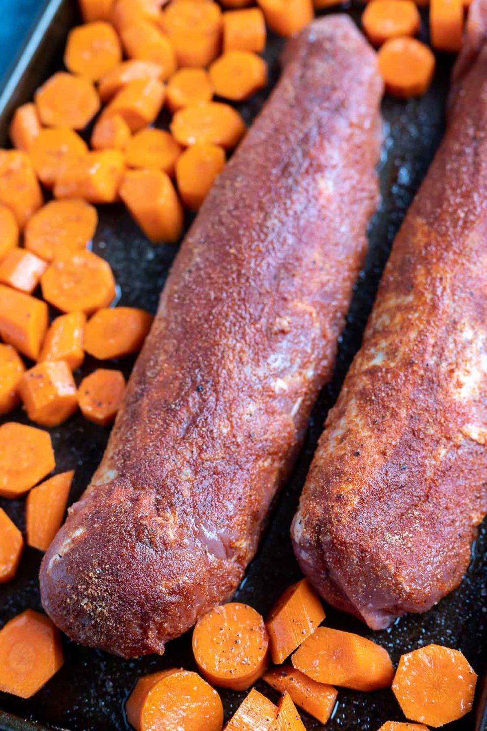 raw pork tenderloin and carrots on sheet pan