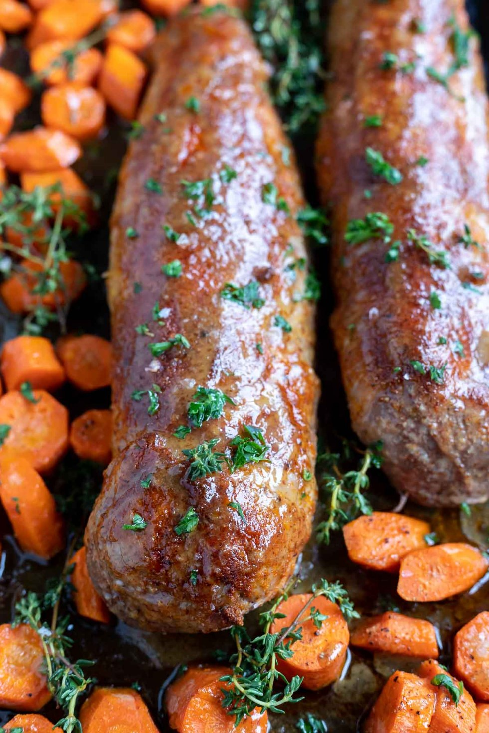 cooked pork tenderloin and carrots on pan