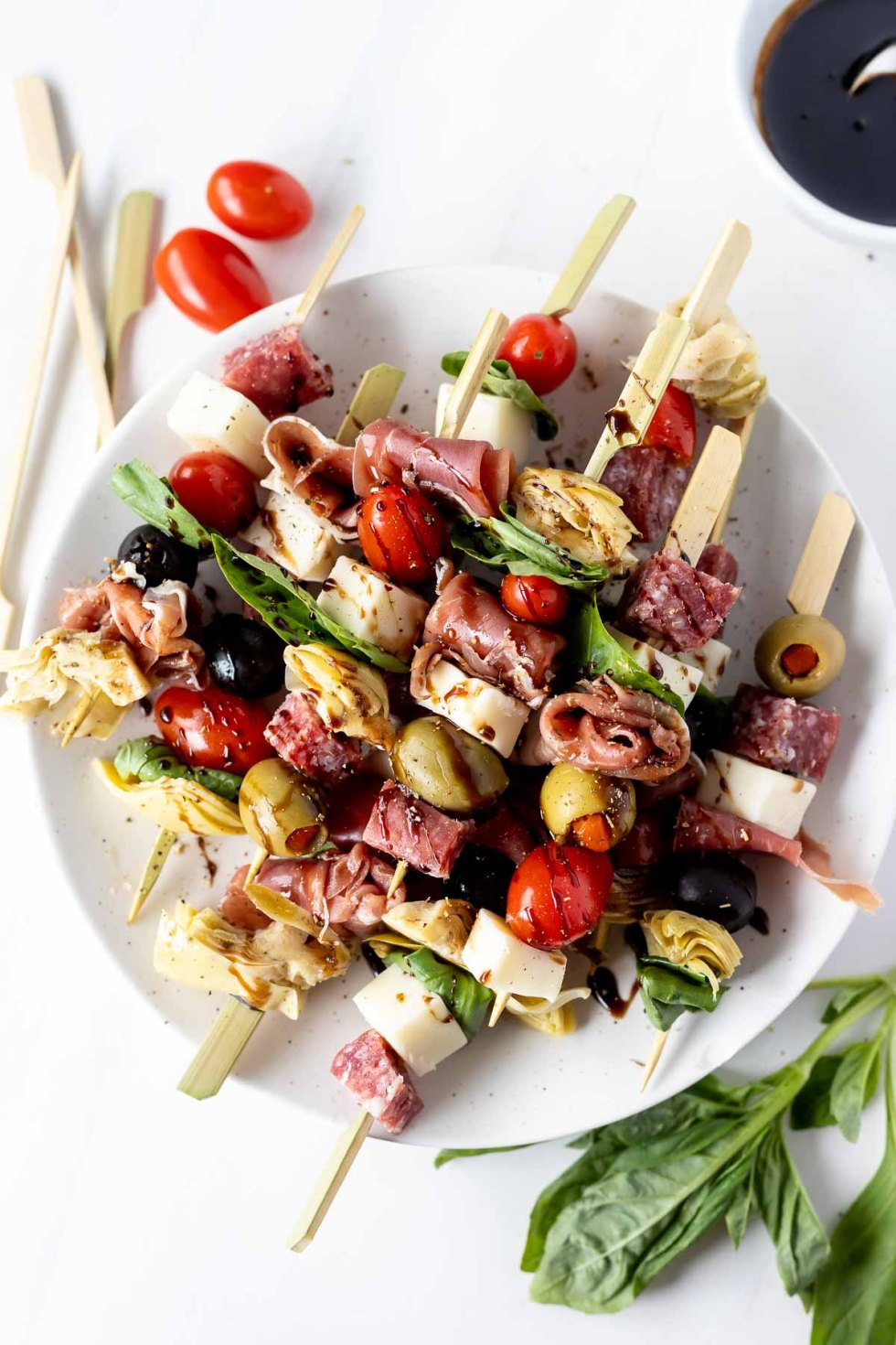 balsamic drizzled antipasto appetizer skewers on white plate