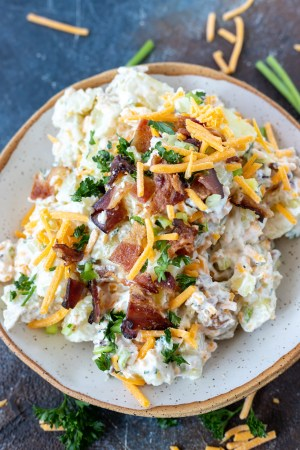 cheese and bacon potato salad in white bowl