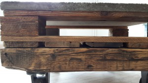 Coachtisch aus Palettenteilen, Rollen aus Gußeisen, Platte aus Beton mit Holzstruktur