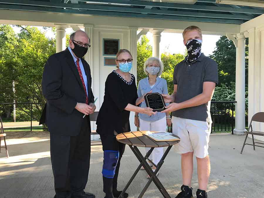 First Selectman Beth Heller (second from left) and Youth Services Director Nancy Pfund present a plaque to AJ Pocwierz, with Scott Zimmerman of Peoples United Bank (left) looking on