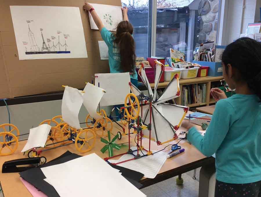 A fourth and second year child preparing a display about wind energy for the MAG Energy Museum.