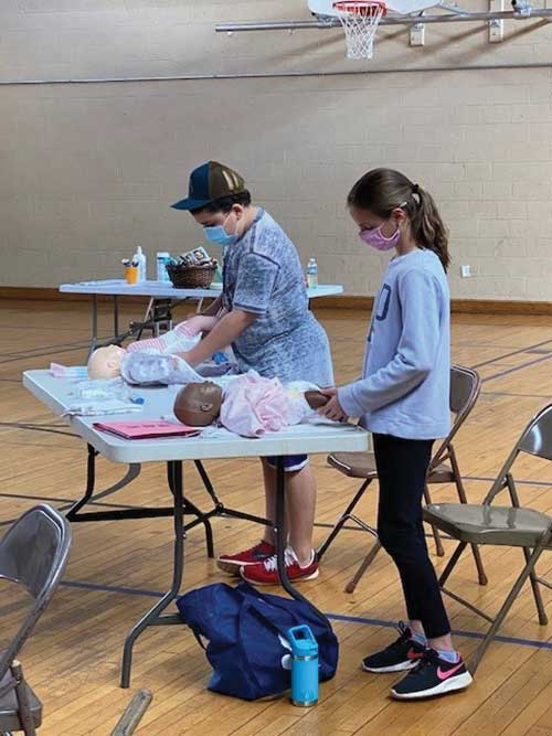 Students learn how to diaper babies in the Red Cross Babysitter Class