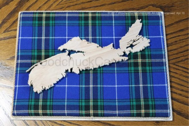 Wood map of Nova Scotia with tartan background