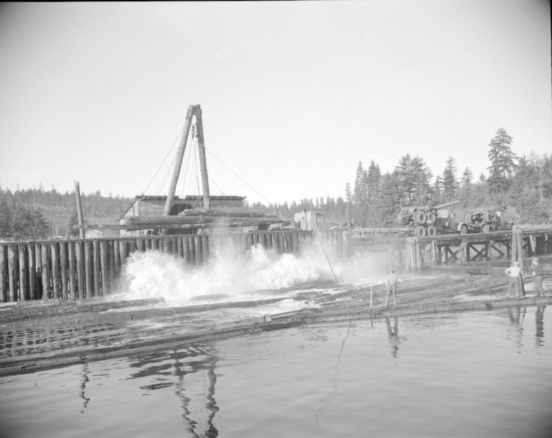 1940s Logs being pushed off a logging truck into the water.