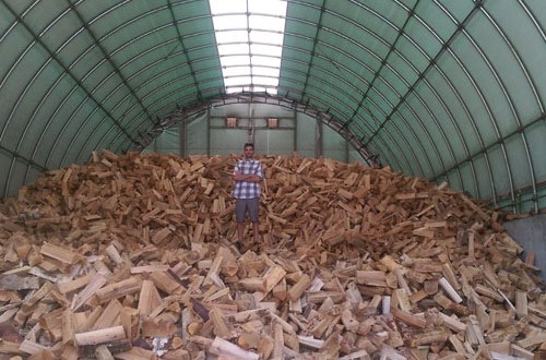 Huge pile of firewood under cover.