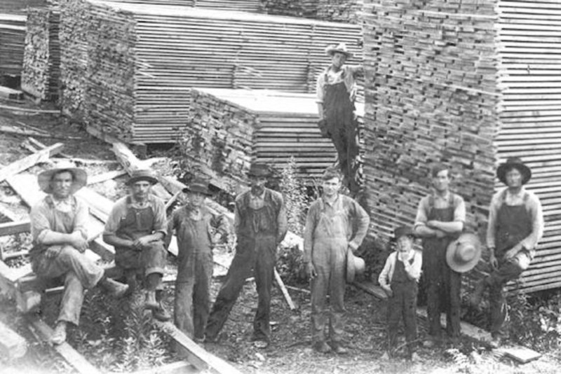 1930 Lumber mill workmen and a child among the group photo.