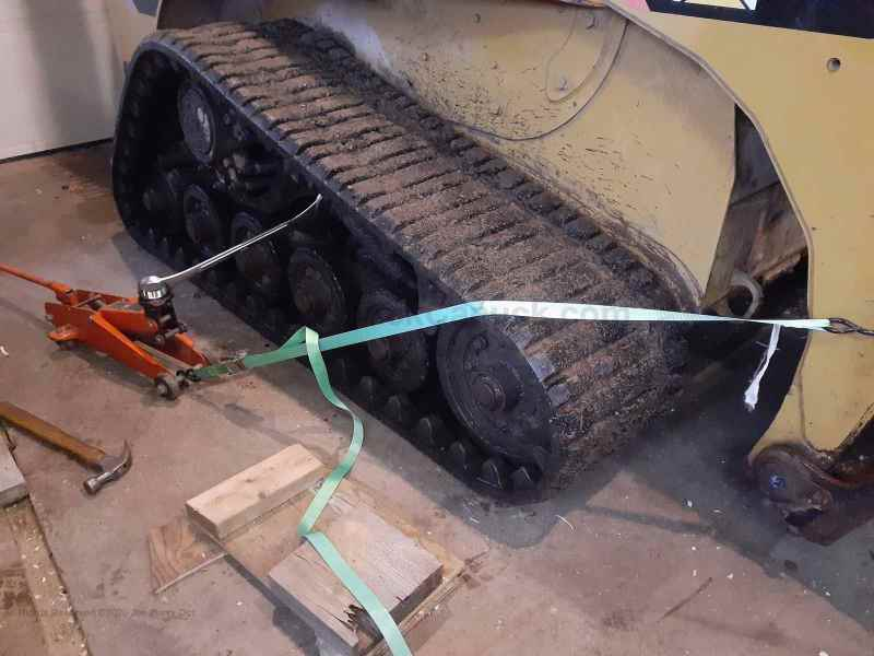 Skidsteer CAT 257B2 track maintenance.