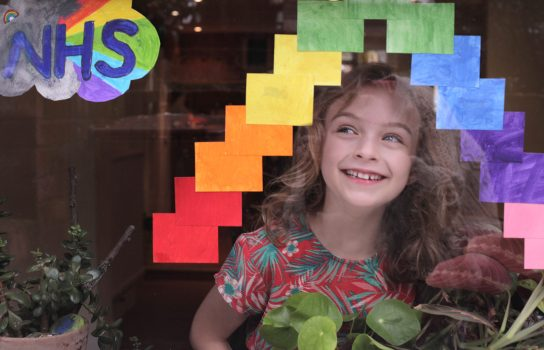 Child smiling through a window with rainbows - dream big at home image