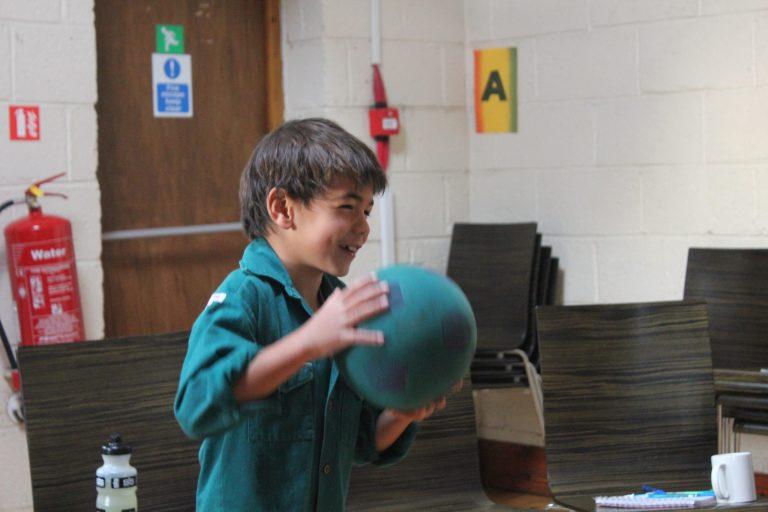 An Elfin in a woodcraft folk shirt, throwing a ball