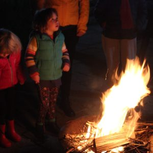 Children gathered round a small campfire at night