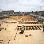 First floor view of timber frame building under construction showing OSB floor and ceiling rafters