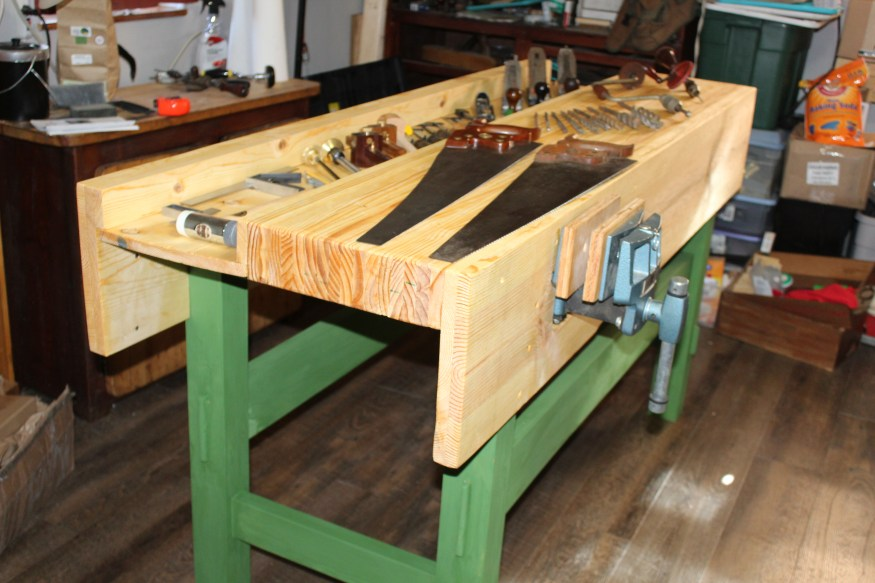 """Pine, roughly 72"""" x 26"""" x 37"""" (I'm 5'6""""). Lower is milk paint, with Boiled Linseed Oil overall. Followed the """"Working Wood"""" workbench, which is very similar to the new videos. Most of the tools are restored from old -- Stanley planes and Disston Saws (the one closest to the vice was found in an antique store for $3, freshly sharpened -- I haven't restored it but used it throughout the bench build."""