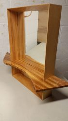 A mirror frame made of Ash with a shelf made of Zebrawood. The shelf is actually inset into the frame and the sides of the frame are beveled to create a depth.