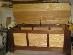 I used ash and walnut to make this paneled blanket chest. All the materials were one inch thick. The bottom was drop in and held in place by cleats that it was attached to with screws. The joinery was primarily mortise and tenon. For the finish I used 2-3 coats of clear Danish oil so the natural colors of the wood could show through.