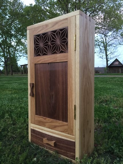 This is a wall cabinet I made for one of my high school teachers as a graduation gift. It's made from oak and walnut and finished with danish oil and wax.
