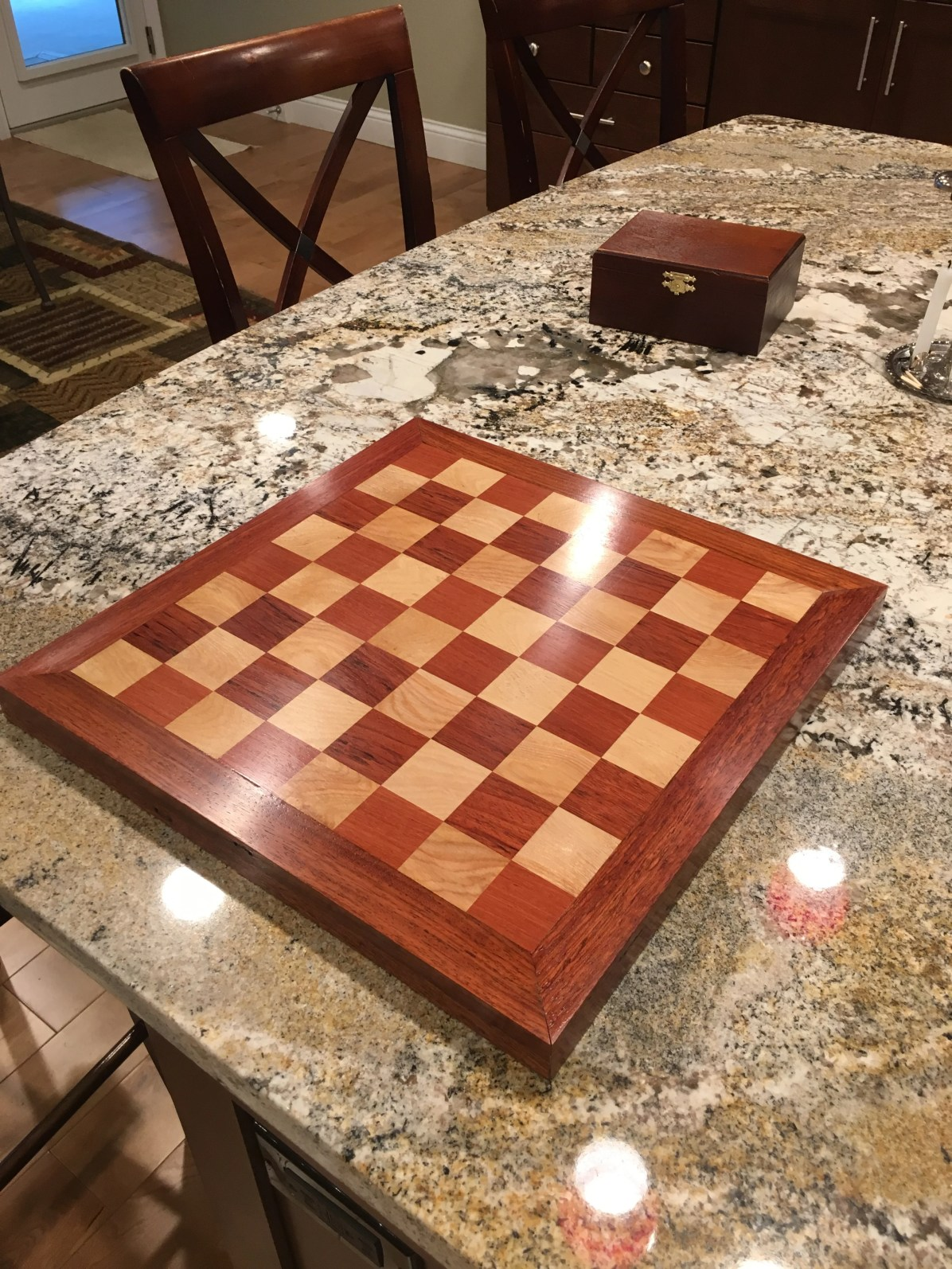 A relative's home suffered significant flooding and required removal of their Brazillian Cherry (Jatoba) hardwood flooring which had some historical sentimental value to them. I salvaged enough of it to make this chess board that might help carry their memories forward. I used the Brazilian Cherry for the border and dark squares, leaving some of the marks and dings in the border to preserve some character from its prior use as a floor, and then some maple I already had for the lighter color. I found the Brazilian Cherry very difficult to work, requiring near constant tool sharpening. Finished with shellac / wax and presented as a Christmas gift last year.