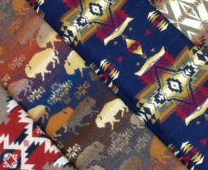 Four Pendleton wool fabrics folded, one with Buffalo, one with stars on a navy background