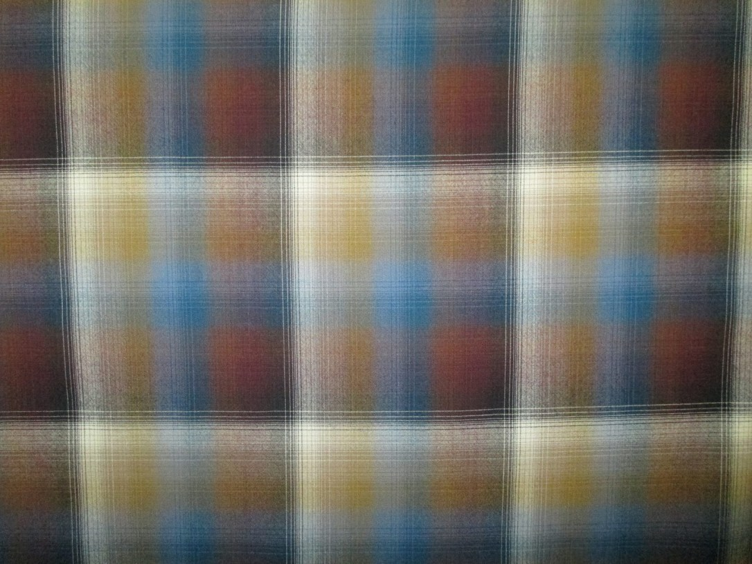 Swatch of Pendleton wool fabric in a large block plaid ombre of gold, blue and rest, with lines of white.