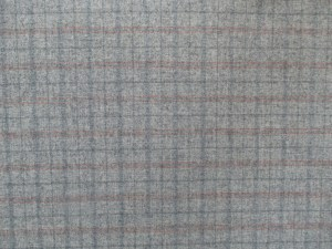 Swatch of Pendleton wool fabric in a tattersall check of dark grey and red on an oxford grey background.