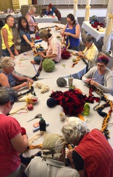 Tables of crafters work together on a group crocheting project in a workshop led by Bonnie Meltzer.